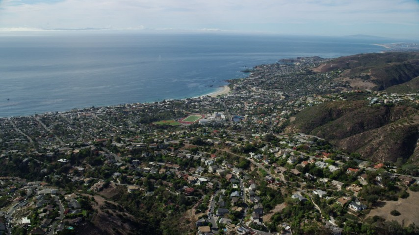 8K stock footage aerial video flying over homes of coastal community towards ocean, Laguna Beach, California Aerial Stock Footage | AX0159_216