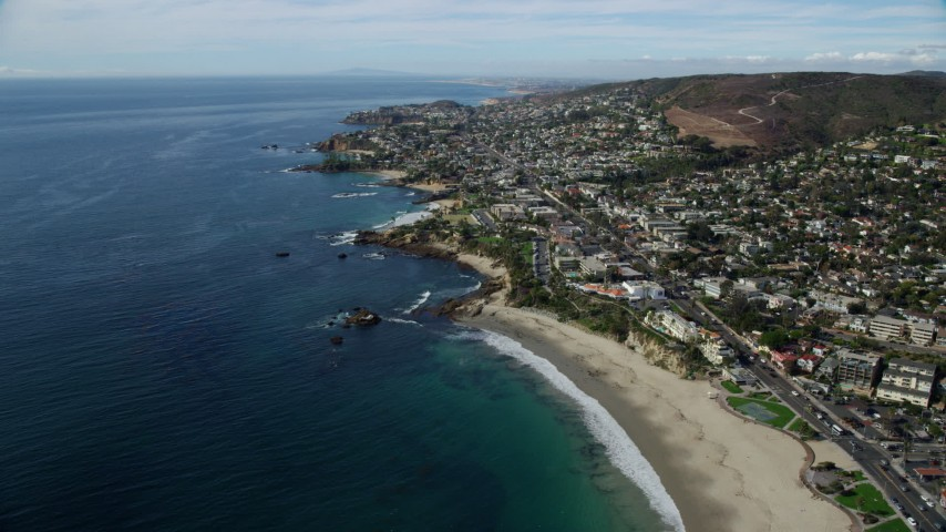8K aerial video flying away from beach to show coastline and beachfront communities, Laguna Beach, California Aerial Stock Footage | AX0159_222