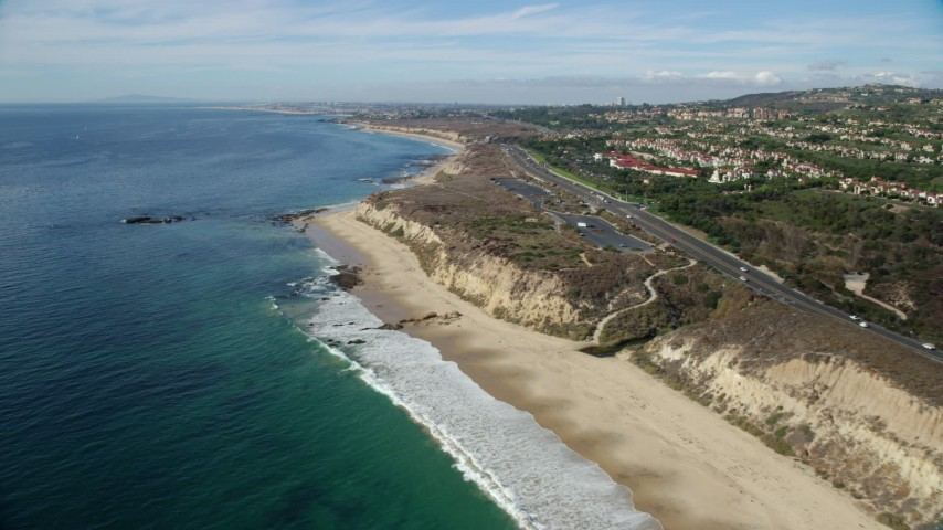8K stock footage aerial video flying over beach along coastal highway, Newport Beach, California Aerial Stock Footage AX0159_228 | Axiom Images