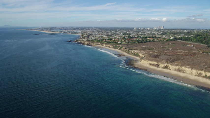 8K stock footage aerial video flying over ocean approaching beachside historic district, Pelican Point, Newport Beach, California Aerial Stock Footage | AX0159_231