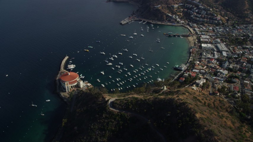 8K stock footage aerial video of a reverse view of the harbor and the coastal town of Avalon, Catalina Island, California Aerial Stock Footage | AX0159_253