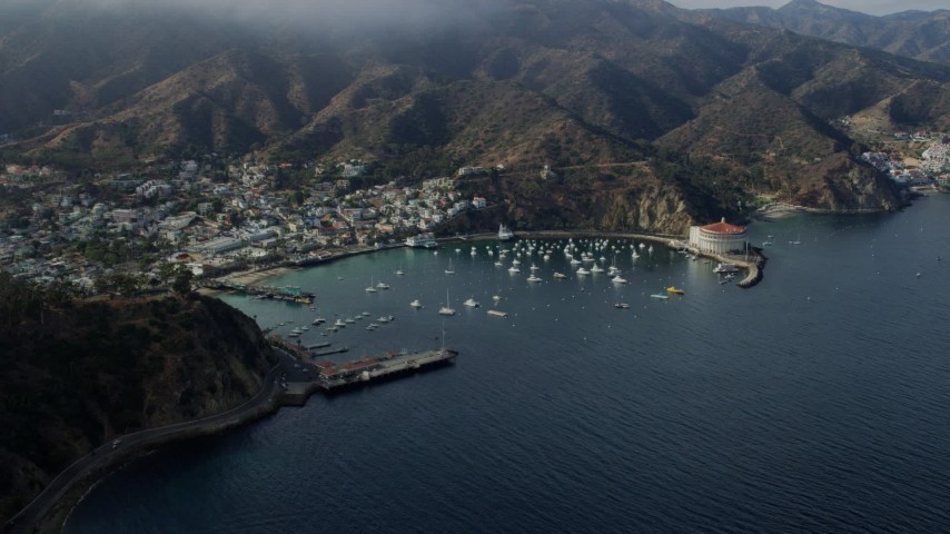 8K stock footage aerial video of a reverse view of boats anchored in Avalon Bay in Avalon, Catalina Island, California Aerial Stock Footage | AX0159_257