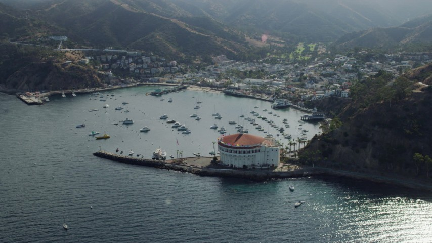 8K stock footage aerial video approaching boats anchored in Avalon Bay harbor by the island town on Santa Catalina Island, California Aerial Stock Footage AX0159_262 | Axiom Images