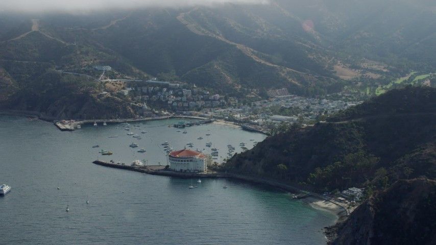 8K stock footage aerial video flying away from the small island town of Avalon, Santa Catalina Island, California Aerial Stock Footage | AX0159_265