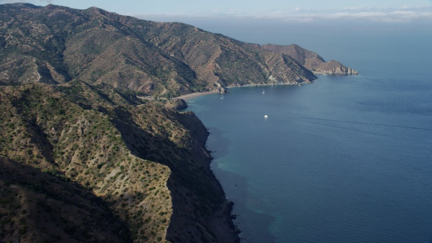 8K stock footage aerial video following the rugged coastline of Santa Catalina Island, California toward a campground Aerial Stock Footage | AX0159_267