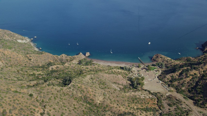 8K stock footage aerial video of a reverse view of a campground, beach, and sailboats on the coast of Santa Catalina Island, California Aerial Stock Footage | AX0159_269