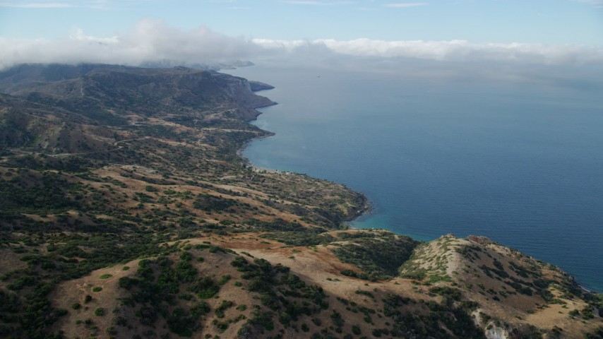 8K stock footage aerial video approaching the coast from hills on Santa Catalina Island, California Aerial Stock Footage | AX0160_002