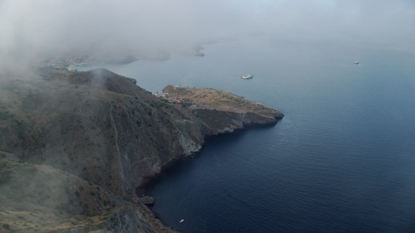 8K stock footage aerial video flying by coastal cliffs to approach the marine science center in Two Harbors, Santa Catalina Island, California Aerial Stock Footage | AX0160_006