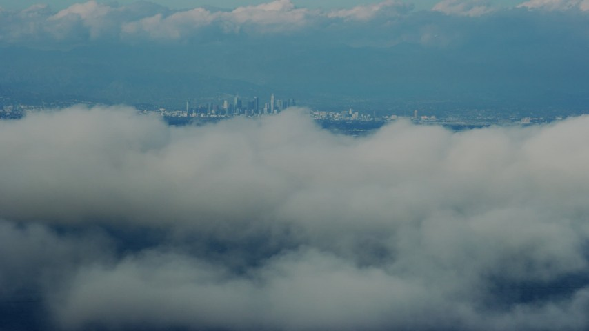 8K stock footage aerial video flying by clouds with a view of Downtown Los Angeles skyline, California Aerial Stock Footage | AX0160_026