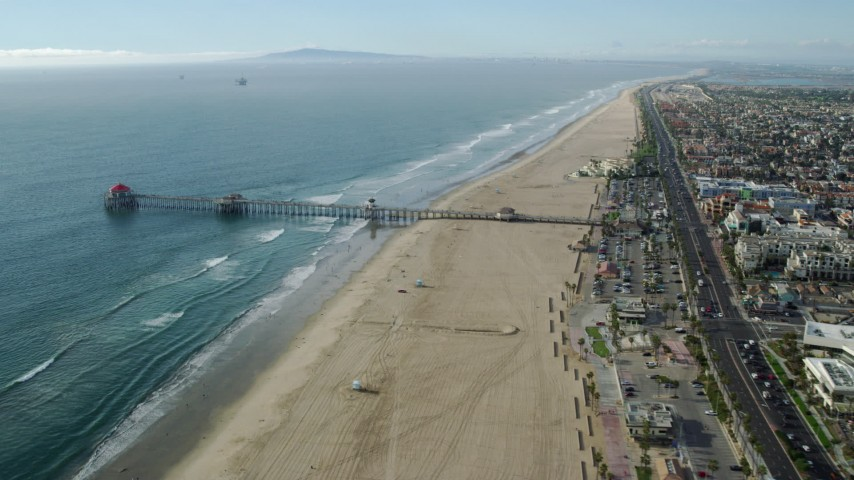 8K stock footage aerial video of Huntington Beach Pier and the beach in Huntington Beach, California Aerial Stock Footage AX0160_041 | Axiom Images