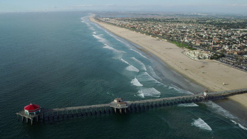 8K stock footage aerial video flying around Ruby's Diner on Huntington Beach Pier for a view of the beachside city, Huntington Beach, California Aerial Stock Footage | AX0160_042
