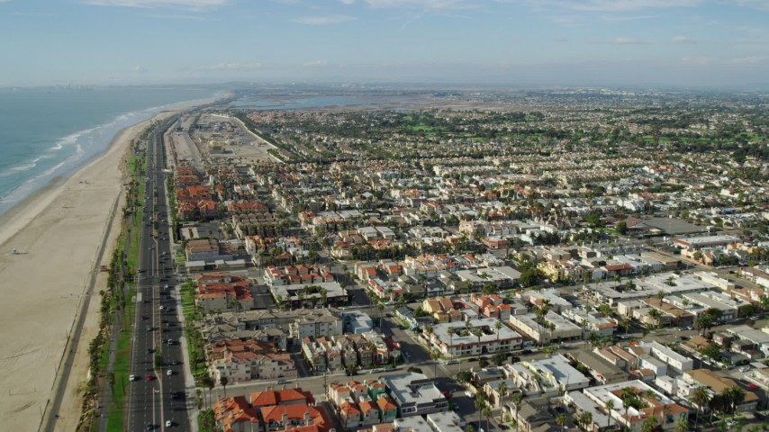 8K stock footage aerial video flying over the beach, Highway 1, and the oceanfront city of Huntington Beach, California Aerial Stock Footage AX0160_043 | Axiom Images