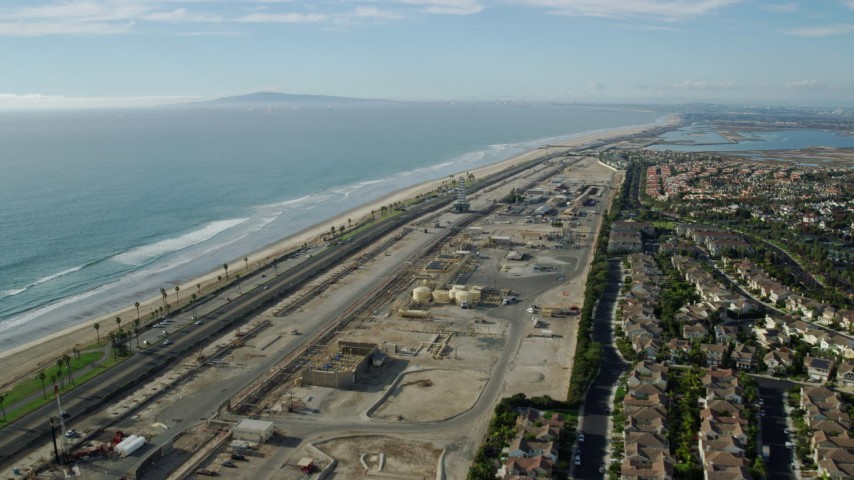 8K stock footage aerial video of homes around an industrial area next to the beach and Hwy 1, Huntington Beach, California Aerial Stock Footage | AX0160_044