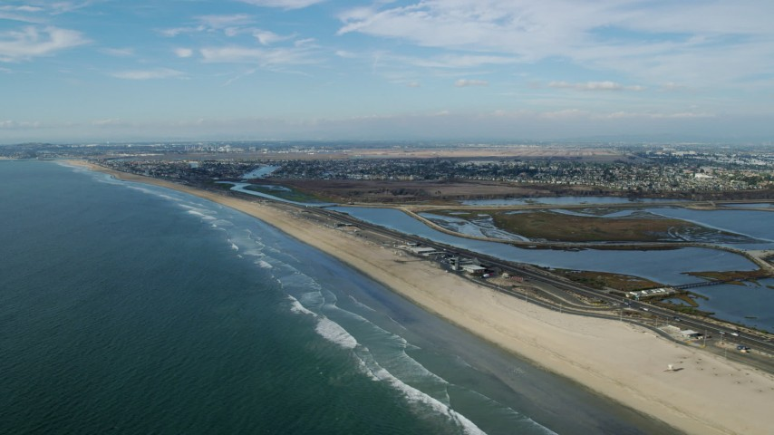 8K stock footage aerial video of Hwy 1 between the beach and Bolsa Chica Ecological Reserve, Huntington Beach, California Aerial Stock Footage | AX0160_048