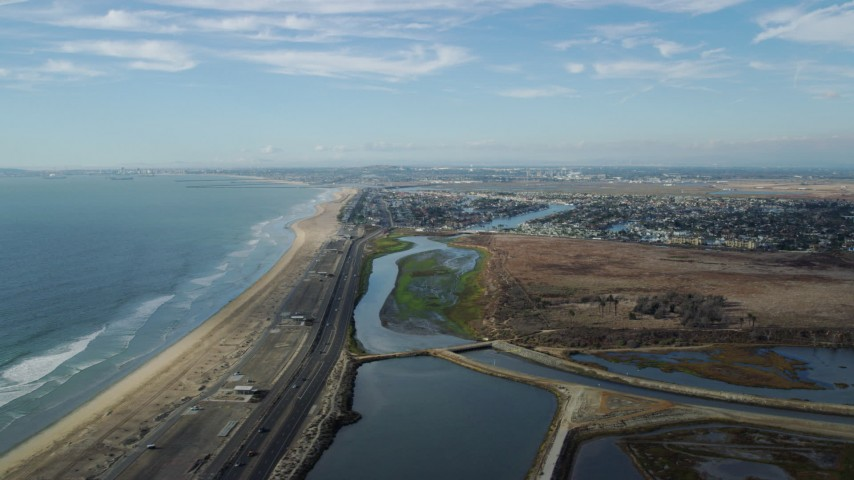 8K stock footage aerial video of the beach and Hwy 1 by Bolsa Chica State Marine Conservation Area, Huntington Beach, California Aerial Stock Footage AX0160_049 | Axiom Images