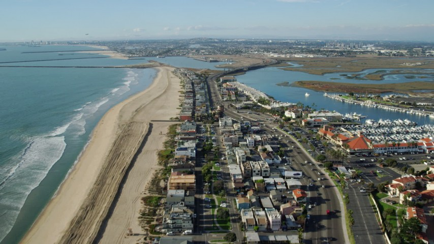 8K stock footage aerial video over beachfront homes and highway to approach Seal Beach National Wildlife Refuge, Huntington Beach, California Aerial Stock Footage | AX0160_052