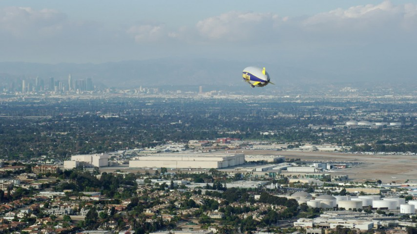 8K aerial video of the Goodyear Blimp approaching the airport, Downtown LA skyline in background, Long Beach, California Aerial Stock Footage | AX0160_061