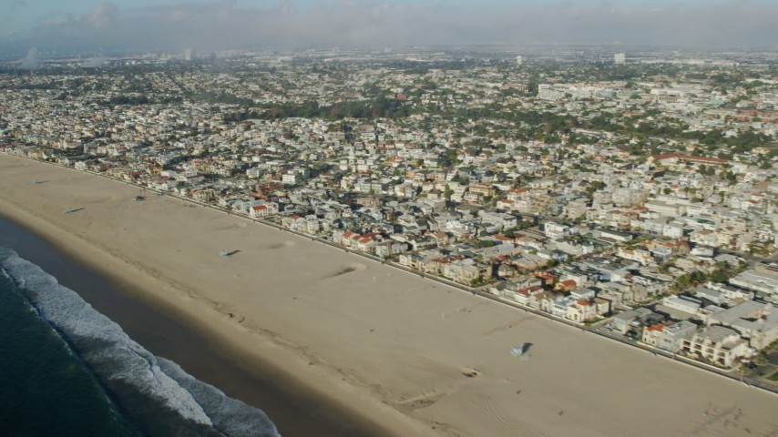 8K stock footage aerial video flying over the beach and coastal neighborhoods in Hermosa Beach, California Aerial Stock Footage AX0161_039