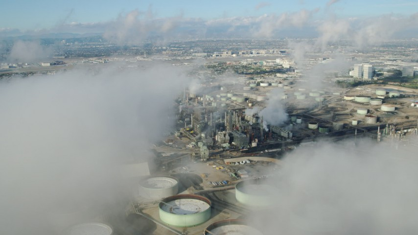 8K stock footage aerial video flying over low level clouds to reveal the Chevron oil refinery in El Segundo, California Aerial Stock Footage | AX0161_042