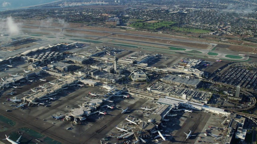 8K stock footage aerial video flying over runways toward the control tower and terminals at LAX, California Aerial Stock Footage | AX0161_046