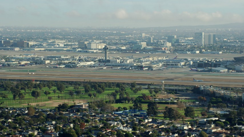 8K stock footage aerial video of LAX Airport as an airliner touches down on the runway, California Aerial Stock Footage | AX0161_050
