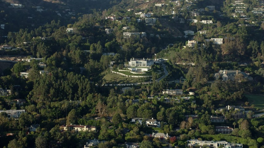 8K aerial video flying by a large hillside mansion with manicured grounds in Beverly Hills, California Aerial Stock Footage | AX0161_108