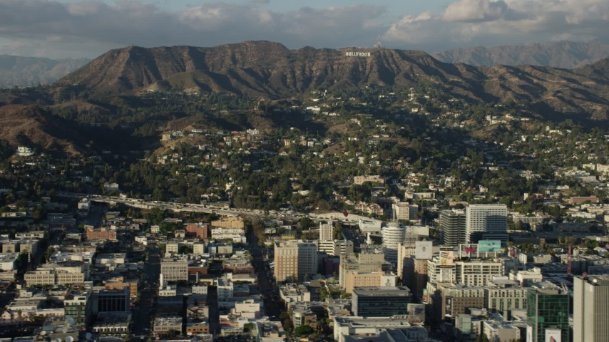 8K stock footage aerial video of the Hollywood Sign, hillside homes, and office buildings in Hollywood, California Aerial Stock Footage | AX0161_121