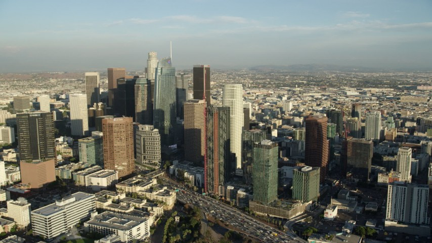 8K aerial video flying by the tall skyscrapers in Downtown Los Angeles, California, and reveal slow traffic on 110 Aerial Stock Footage | AX0162_005