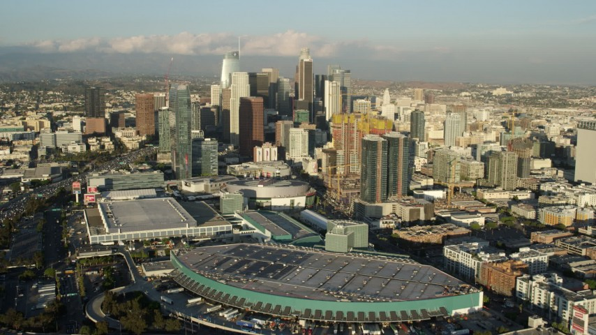 8K stock footage aerial video flying over Staples Center and Oceanwide Plaza to approach skyscrapers, Downtown Los Angeles, California Aerial Stock Footage | AX0162_018