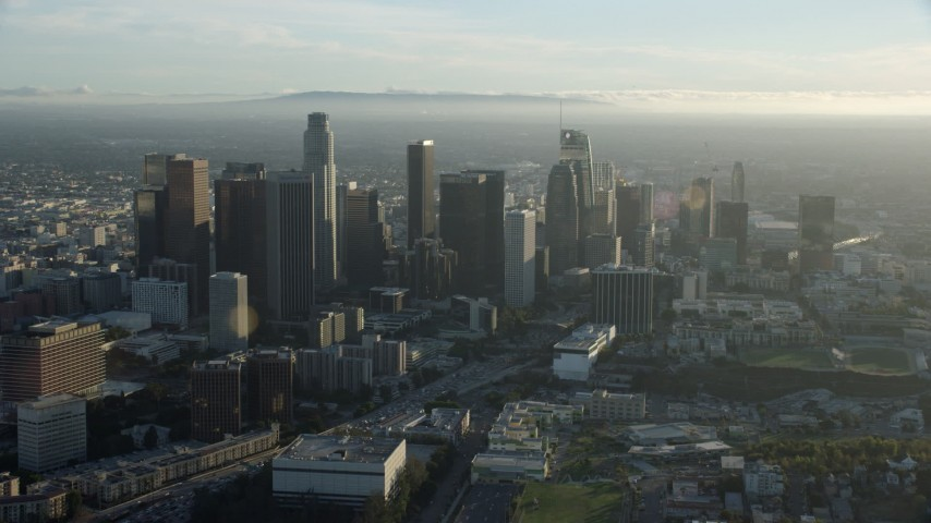 8K stock footage aerial video flying away from skyscrapers on a hazy day in Downtown Los Angeles, California Aerial Stock Footage | AX0162_022