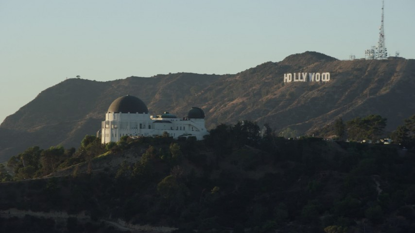 8K stock footage aerial video flying by the Griffith Observatory to reveal the Hollywood Sign in Los Angeles, California Aerial Stock Footage | AX0162_049