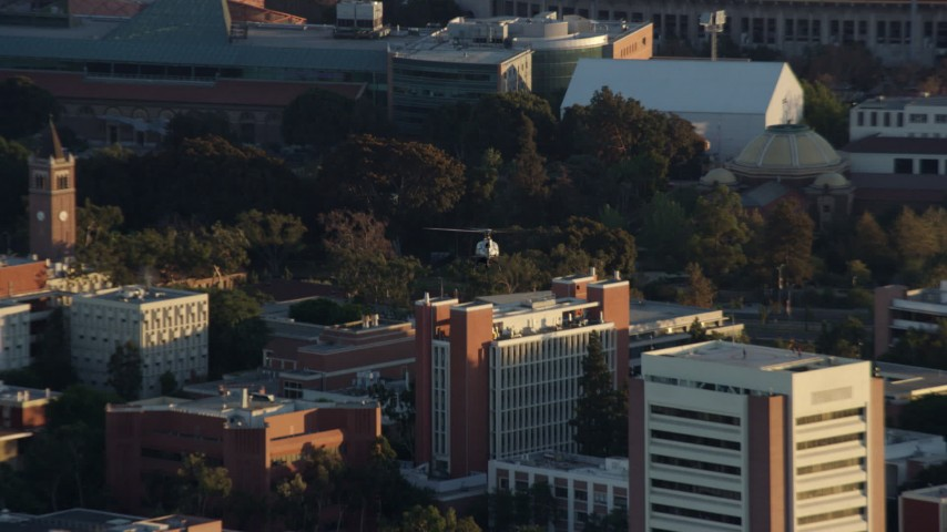 8K aerial video tracking an LAPD helicopter flying over USC in University Park, Los Angeles, California Aerial Stock Footage AX0162_062
