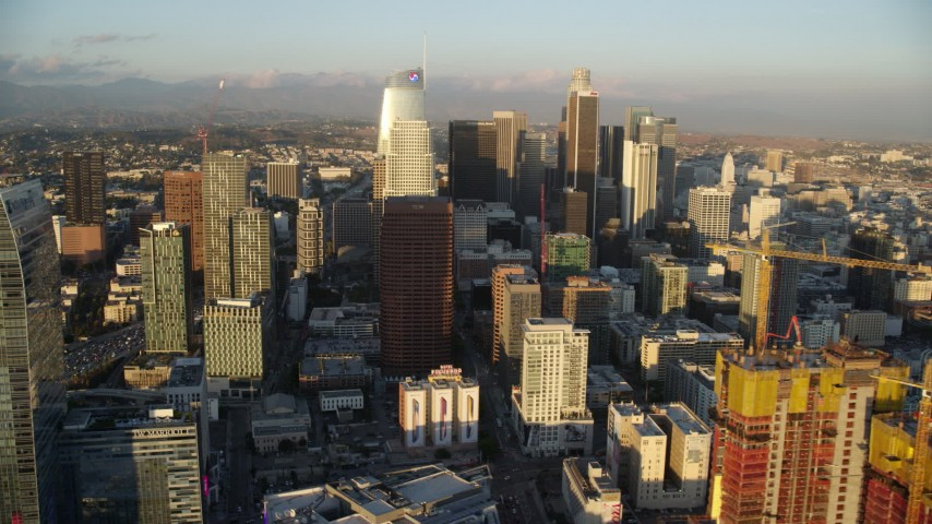 8K stock footage aerial video of skyscrapers seen while flying by The Ritz-Carlton Hotel at sunset in Downtown Los Angeles, California Aerial Stock Footage | AX0162_070