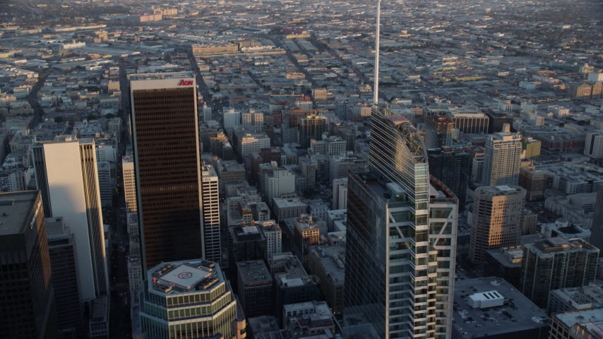8K stock footage aerial video of a city sprawl beyond the tops of Aon Center and Wilshire Grand Center at sunset in Downtown Los Angeles, California Aerial Stock Footage | AX0162_081