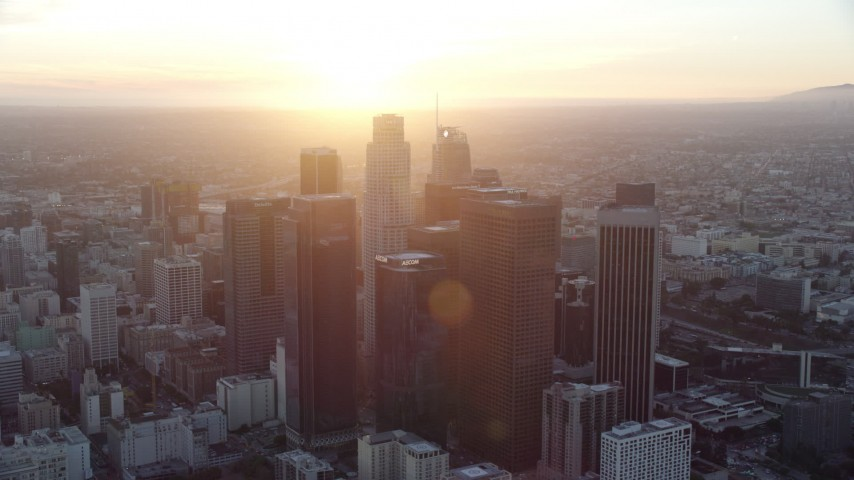 8K stock footage aerial video of a reverse view of the tall towers of downtown at sunset in Downtown Los Angeles, California Aerial Stock Footage AX0162_085 | Axiom Images