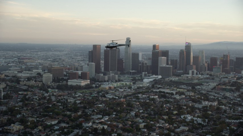 8K stock footage aerial video tracking an LAPD helicopter flying by the skyline of Downtown Los Angeles, California at twilight Aerial Stock Footage | AX0162_092