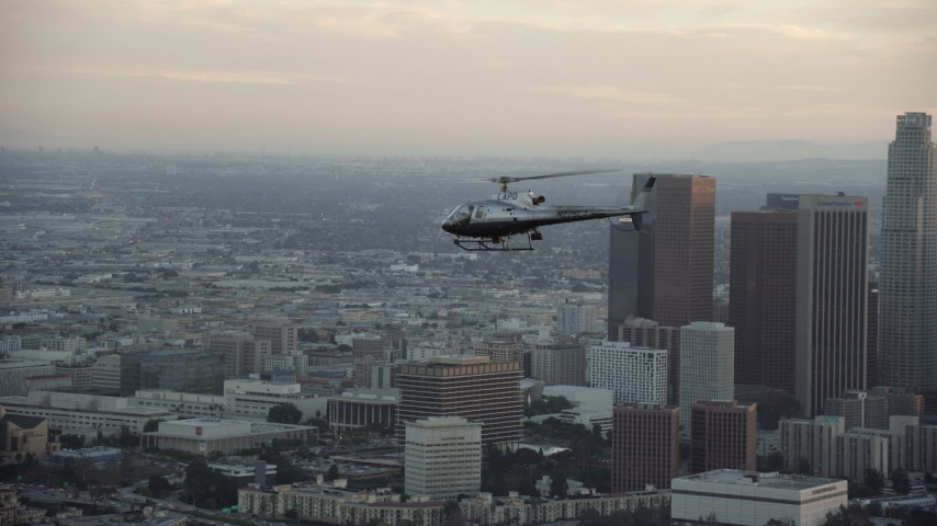 8K stock footage aerial video of an LAPD helicopter flying by the skyline of Downtown Los Angeles, California at twilight Aerial Stock Footage | AX0162_093