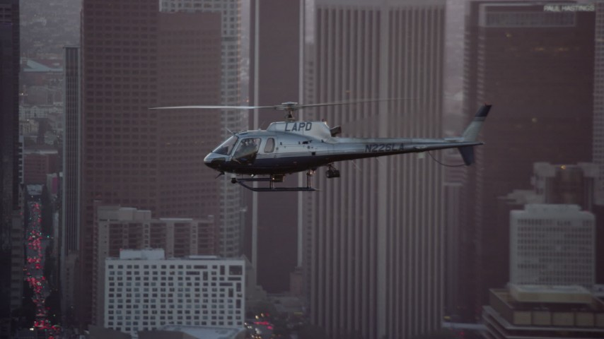 8K stock footage aerial video tracking an LAPD helicopter flying by Downtown Los Angeles, California at twilight Aerial Stock Footage | AX0162_095