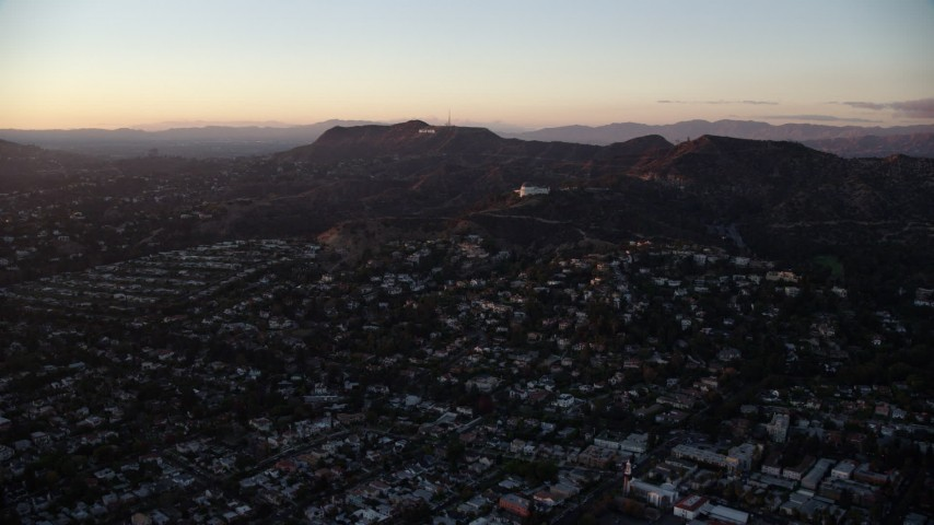 8K stock footage aerial video flying over Los Feliz to approach the Hollywood Sign and Griffith Observatory in Los Angeles, California at twilight Aerial Stock Footage | AX0162_098