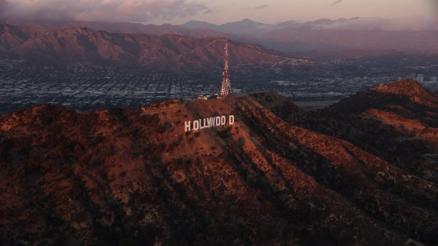 8K stock footage aerial video flying by the famous Hollywood Sign at twilight in Los Angeles, California  Aerial Stock Footage | AX0162_102