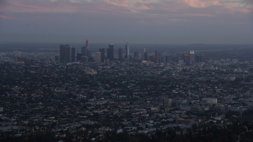 8K stock footage aerial video flying over hilltop palm trees to reveal Downtown Los Angeles, California at twilight Aerial Stock Footage | AX0162_106