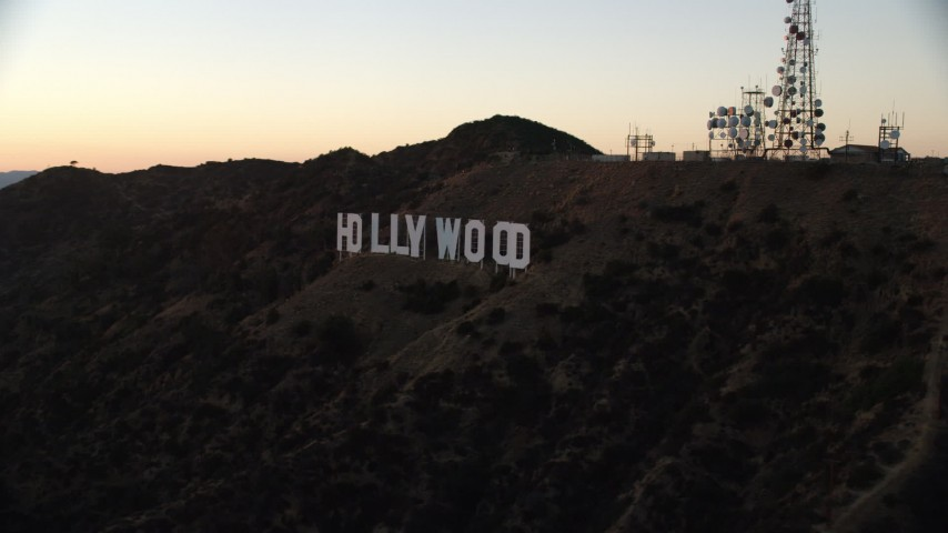 8K stock footage aerial video approaching and flying by the famous Hollywood Sign at twilight in Los Angeles, California  Aerial Stock Footage | AX0162_108