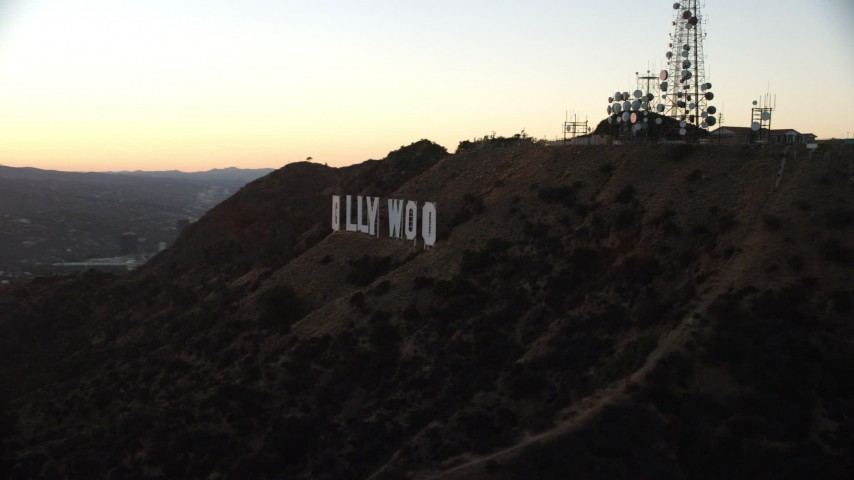 8K stock footage aerial video flying by the famous Hollywood Sign to reveal setting sun in Los Angeles, California  Aerial Stock Footage | AX0162_109