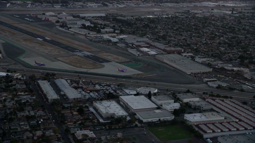 8K stock footage aerial video of commercial airplanes on the end of the runway at Burbank Airport, California, twilight Aerial Stock Footage | AX0162_115