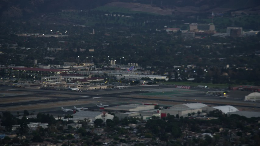 8K stock footage aerial video of a commercial airplane soaring away from Burbank Airport, California at twilight Aerial Stock Footage AX0162_118 | Axiom Images