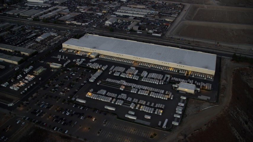 8K stock footage aerial video approaching and passing a large warehouse building in Pacoima, California at twilight Aerial Stock Footage | AX0162_119