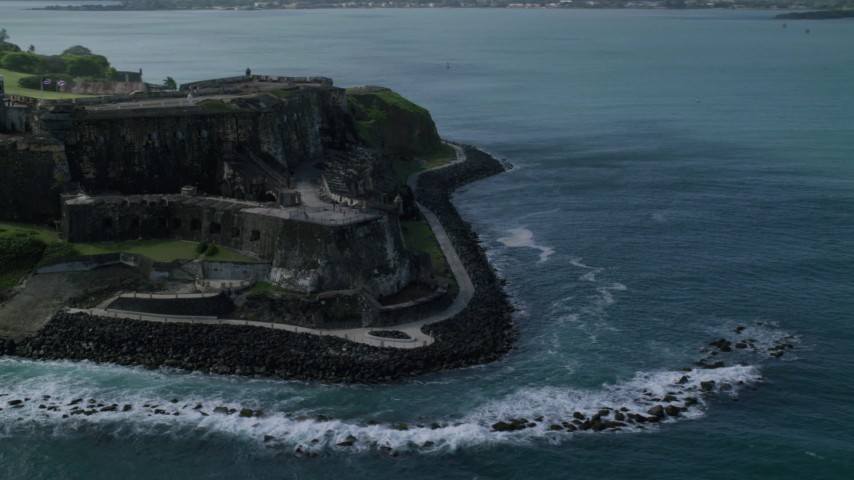 5k Aerial Video of a Historic fort along the coast of clear blue water, Old San Juan Puerto Rico Aerial Stock Footage | AX101_013