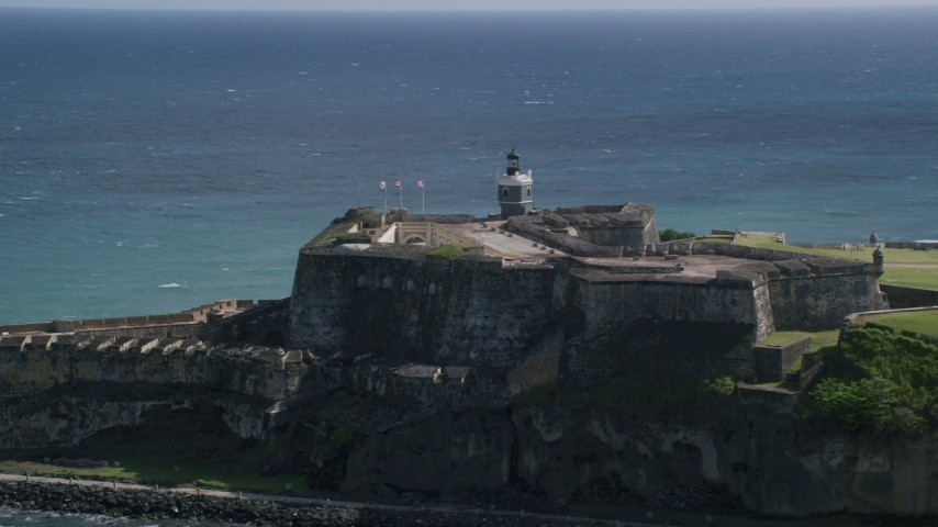 5k Aerial Video of a Historic fort along the coast resting on clear blue water, Old San Juan Puerto Rico Aerial Stock Footage | AX101_016