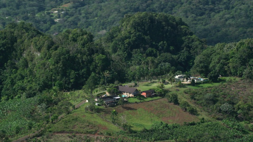 5k aerial video of a Farmhouse nestled in at lush green forest, Karst Forest, Puerto Rico Aerial Stock Footage | AX101_070