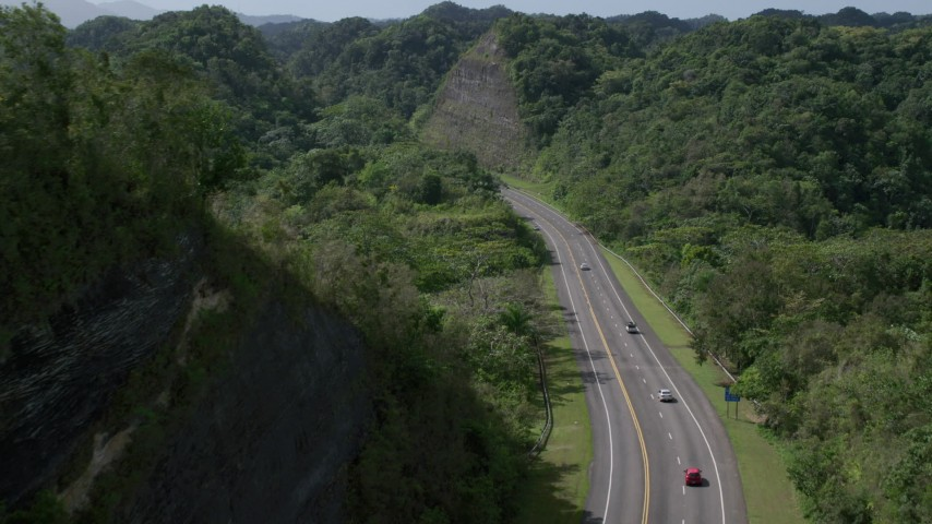 5k stock footage aerial video Following light traffic through lush green mountains, Karst Forest, Puerto Rico Aerial Stock Footage | AX101_079